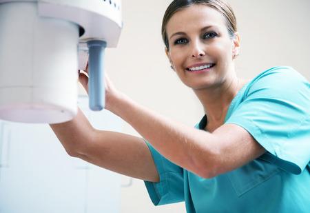 x ray machine: Beautiful female doctor checking x-ray machine.