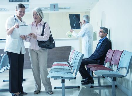 Artsen en patiënten spreken in het ziekenhuis wachtkamer.