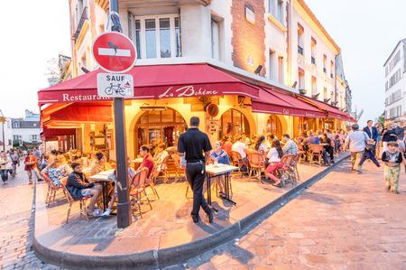 parisian scene: PARIS - JUNE 20, 2014: Tourists explore Montmartre streets at night. Montmartre area once attracted famous modern artists.