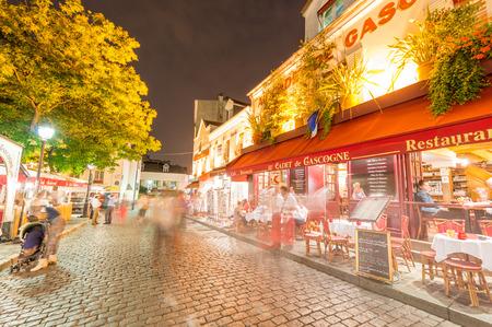 PARIS - 20 juin 2014: Les touristes explorer les rues de Montmartre la nuit. Quartier de Montmartre a attiré une fois de célèbres artistes modernes.