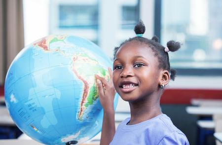 fille noire: Jeune fille noire afro am�ricain � l'�cole souriant toucher un globe terrestre. Banque d'images