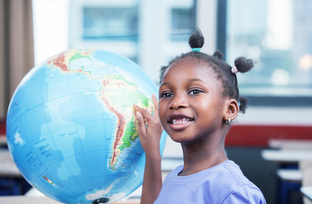 Young afro american black girl at school smiling touching a\ world globe.