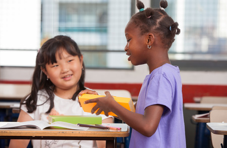 chinese american: Two young multiracial african asian girls smiling at classroom desk.