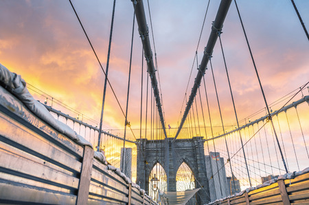 taxi famous building: Magnificent structure of Brooklyn Bridge with sunset sky - NYC. Stock Photo