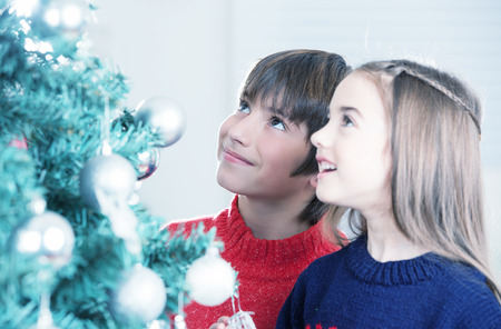 mesmerized: Boy and girl mesmerized by Christmas Tree. Stock Photo
