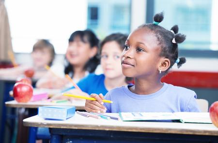 Řada studentů primární interracial třídě. Afro american dívka věnovat pozornost učiteli.