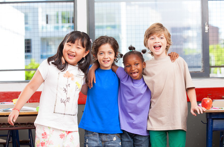 ni�os sonriendo: Multi �tnica aula. Afro ni�os de la escuela primaria americanos, asi�ticos y cauc�sicos feliz sonriendo. Foto de archivo