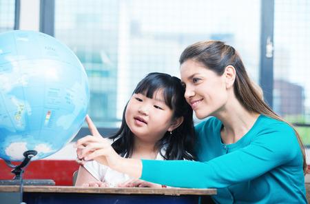 teacher classroom: Elementary school teacher explaining Earth globe to asian female student.