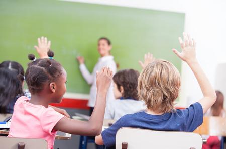 salon de clase: Retrato de los ni�os levantaron la mano en un aula multi�tnica.