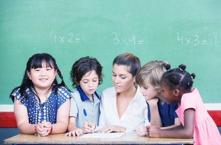 multi ethnic: Multi ethnic classroom with teacher explaining mathematics lesson. Stock Photo