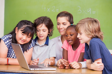 student: Interracial primary classroom learning to use laptop with their teacher. Stock Photo