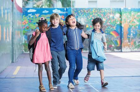 multi race: Felices los ni�os abrazan y que sonr�en en el patio de la escuela primaria. Amistad interracial.