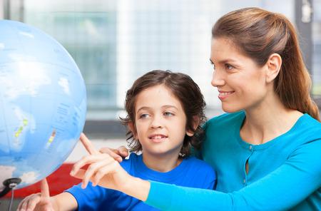 Happy school concept. Female teacher explaining geography to kid photo