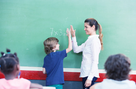 Teacher congratulating with kid in primary classroom.