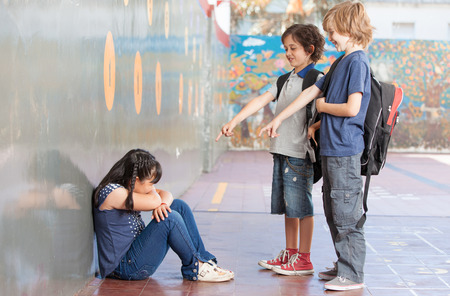 bully: Elementary Age Bullying in Schoolyard. Stock Photo