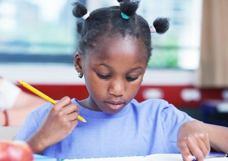 Afro-Amerikaanse vrouwelijke student doet schoolwerk in de klas.