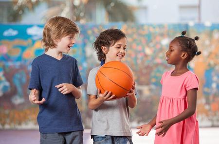 多民族の子供たちは校庭で遊んでの笑みを浮かべてください。