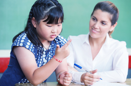 numeracy: Asian female student learning to count with her teacher.