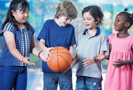 baloncesto chica: Estudiantes de primaria caucásicas, asiáticas y afroamericanas jugar al baloncesto.