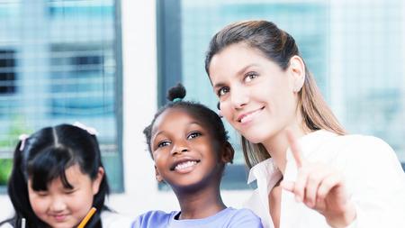 multi race: Concepto de escuela raza m�ltiples feliz. Profesor sonriente con los estudiantes. Foto de archivo