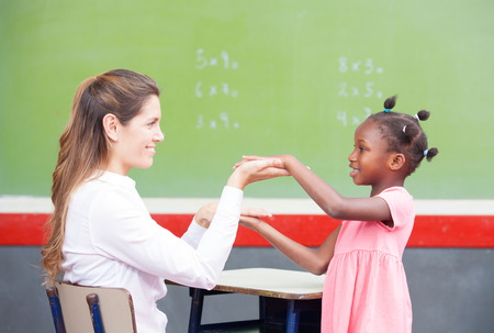 congratulating: Happy teacher and afroamerican elementary student congratulating during math lesson. Stock Photo