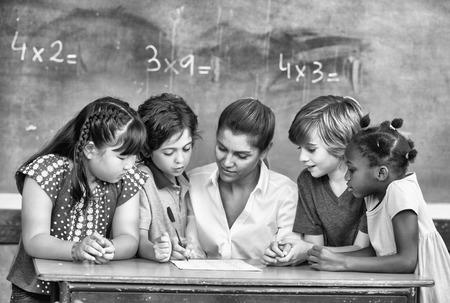 multi race: Atractivo joven maestra de comprobar m�ltiples trabajo en el aula carrera con otros estudiantes en el mostrador.