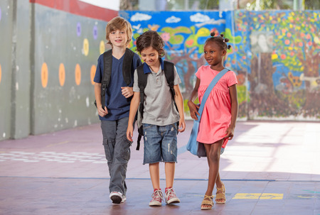 Group of multiracial schoolmates walking and smiling.