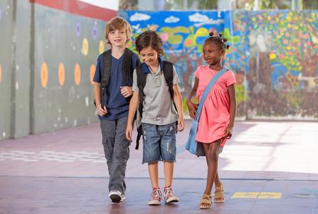 escuela primaria: Grupo de compañeros de escuela multirracial caminando y sonriente.