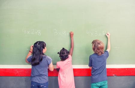 matematicas: Compañeros de escuela étnicos multi escritura matemáticas en pizarra.