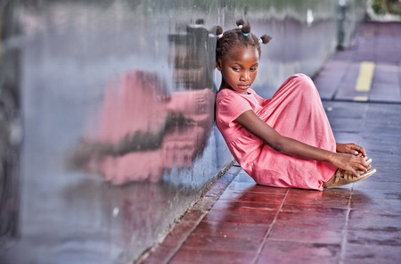 outcast: Sad african girl sitting and deeply thinking on the school floor.
