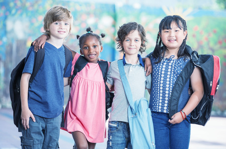 multi ethnic: Happy multi race classroom embracing in the schoolyard.