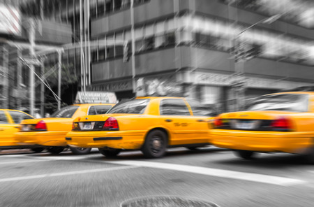 Zoomed and blurred view of New York yellow cabs isolated on black and white background.