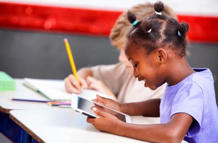 ni�os negros: Multi estudiantes de primaria �tnicos juegan con la tablilla y la escritura.