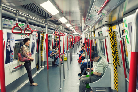 reportedly: HONG KONG - APRIL 22, 2014: Riders on the MTR in Hong Kong, China. In 2012 the MTR reportedly had 46.4% of the public transport market, making it the most popular transport in Hong Kong