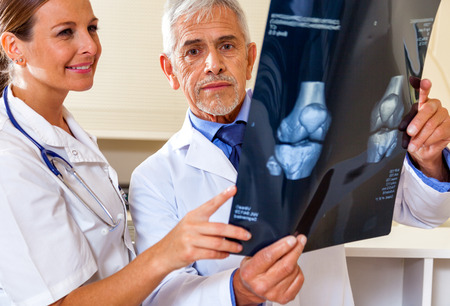 Expert doctor analyzing x-ray scan with female assistant. photo