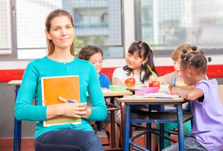 Happy teacher in elementary classroom. photo