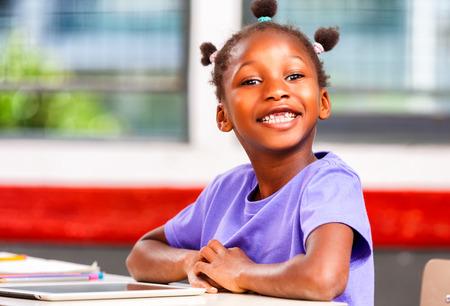 negras africanas: Muchacha afroamericana en la escuela primaria feliz en su escritorio.