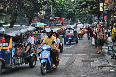 fare: BANGKOK - AUG 23: A three wheeled tuk tuk taxi transports passengers along road, August 23, 2012 in Bangkok, Thailand. Tuk tuks can be hired from as little as $1 or B30 a fare for short trips