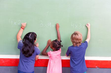 matematicas: Niños de la escuela de la raza mezclada que escriben en la pizarra.
