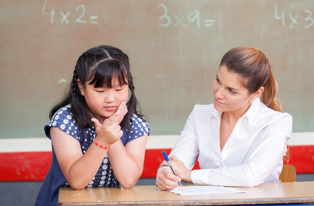 Chinese girl learning math with teacher. photo