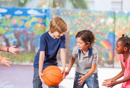 Elementary school children happy playing basketball at school.