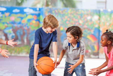 educacion fisica: Los niños de primaria de baloncesto feliz jugando en la escuela.