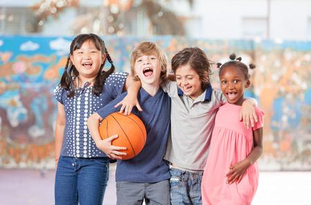 Basisschool kinderen gelukkig spelen basketbal op school. Stockfoto