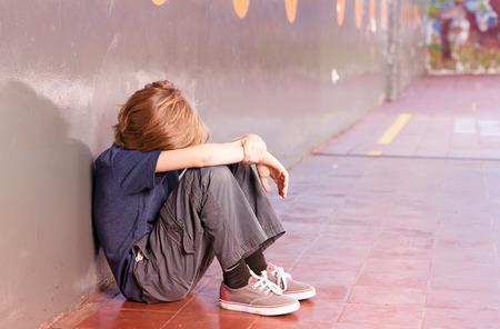 niños tristes: Niño de escuela primaria solo en la escuela. Concepto de aislamiento.