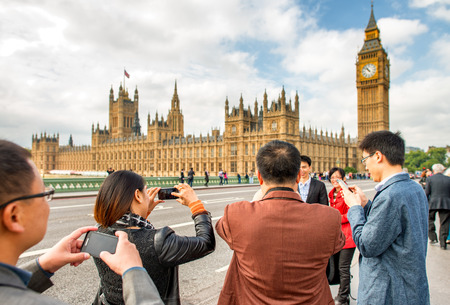 westminster city: LONDON - SEPTEMBER 29, 2013: Tourists walk along Westminster Bridge. The city is visited by more than 30 million people annually.