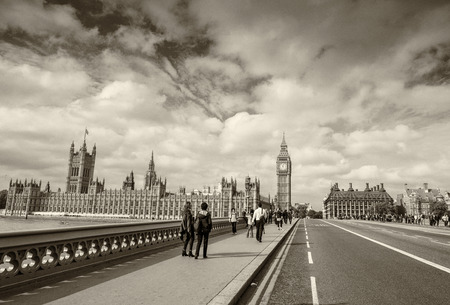 city of westminster: LONDON - SEPTEMBER 29, 2013: Tourists walk along Westminster Bridge. The city is visited by more than 30 million people annually.