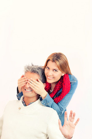 guess: Guess who? Beautiful young woman covering eyes of her boyfriend and smiling. Isolated on white. Stock Photo