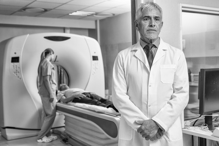 technologists: Confident male doctor in hospital with patient undergoing mri.