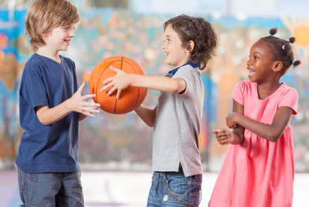 baloncesto chica: Varios niños étnicos felices que juegan al baloncesto en la escuela. Foto de archivo