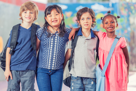 pre teens: Happy group of multi ethnic children together at school. Stock Photo